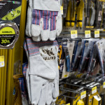 Work gloves that have been branded with the Immigrant Crossing Sign are placed back on the shelves of Home Depot.