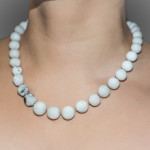 A set of pearls are carved from white erasers then knotted and strung onto silk. Some pearls have black marks from pencil lead on them. Photographed on the body with a grey background.