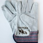 A pair of brand new leather work gloves are branded with the Immigrant Crossing Sign and photographed on at white background.