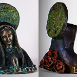 A bronze bust of the Virgin Mary with an aztec calendar as a halo, roses on her back, and an El Camino emblem on her chest is seen on a white background.