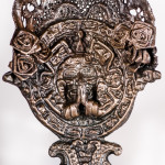 An assemblage sculpture of Catholic religious iconography and Mexican cultural iconography on white background.