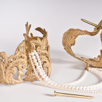 A pair of cast bronze lace handcuffs hinged with fabricated nail closures attached together by a strand of pearls on a white background.