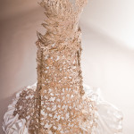 a cast lace white bronze metal wedding dress on a cream background with sateen under.