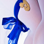 A cast lace piece attached to a garter of royal blue ribbon on female legs wearing white tights on a white background.